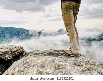 Man hiker legs with windproof trousers and hiking boots on mountain peak rock with a valley at background