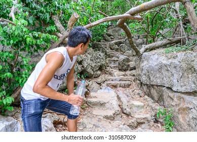 Man hiker looking ahead atfer drinking water in roasting day.