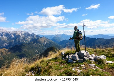 Man hiker, near the rood of top, on mountain top watching the mountain range.