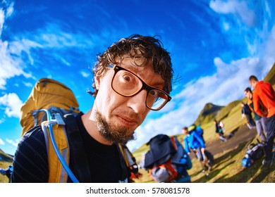 man hiker on the trail, hiking in Iceland. man packs his backpack. man in glasses with funny face looking at the camera