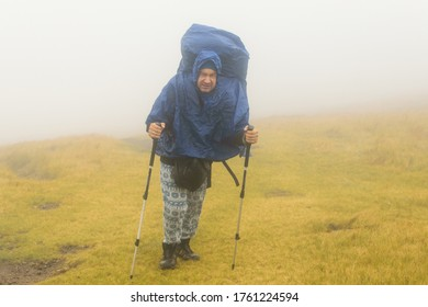 A man hiker in a rain cover in the fog during bad weather.
