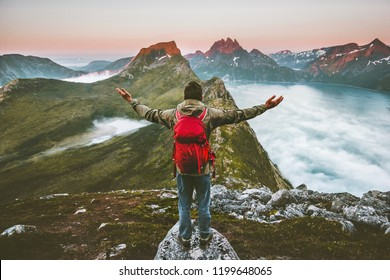 Man hiker raised hands exploring mountains of Norway Traveling healthy lifestyle adventure concept hiking with backpack active vacations outdoor