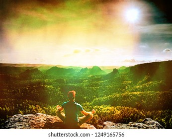Man hiker sitting on a rock in mountain. Abstract, over filtered. Man sit. Fall mountain mist. Mist in valleys