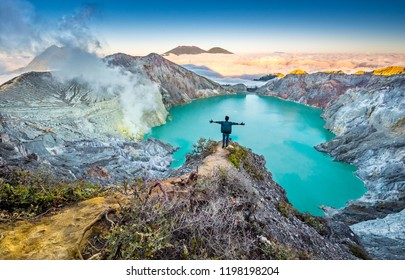 Man hiker staying on crater cliff with spread his arms. Panorama of colourful sunrise daybreak on the edge of volcano over acid lake in Kawah Ijen crater, Java, Indonesia. Smoke from sulphur mining.