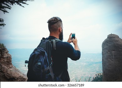 man hiker taking photo with smart-phone at mountain peak cliff