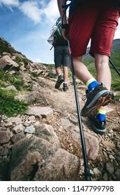 Man hiker walking on mountain rocks with sticks. Beautiful weather with Scotland nature. Detail of hiking boots on the difficult pathway, trail, Friends in the nature and enjoying sport.