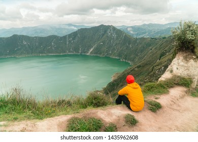 Man hiker in yellow looking at dramatic perspective of Quilotoa lake and volcano crater, with view of mountains, hiking loop from viewpoint. Shot in Ecuador. Green and blue. Freedom adventure concept.
