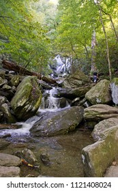 A man hikes to Catawba Falls, one of Western North Carolina's beautiful, scenic Blue Ridge Mountain waterfalls that cascades over 100 ft onto rocks and logs