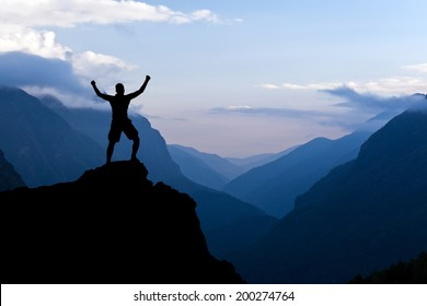 Man hiking accomplish success silhouette in mountains. Male hiker with arms outstretched on top of mountain looking at beautiful Himalayan landscape.
