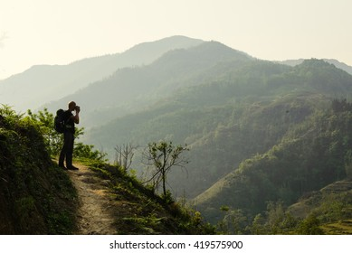Man hiking with backpack holding photo camera and taking picture of the green mountains in summer. Landscape photography during a short break