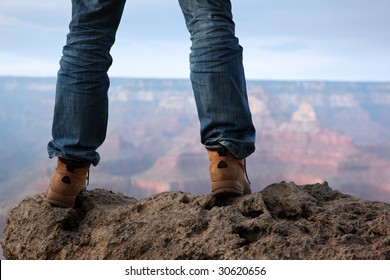Man in hiking boots standing on edge of a cliff in Grand Canyon, Arizona.