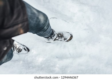 Man in hiking boots walking in snow.
