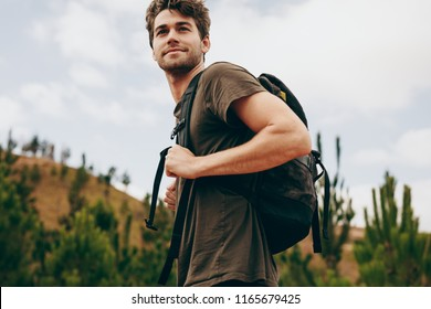 Man hiking in a countryside location. Side view of a man wearing a bag walking through a forest.