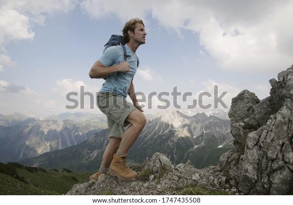 Man hiking up mountain, Kleinwalsertal, Allgau, Germany