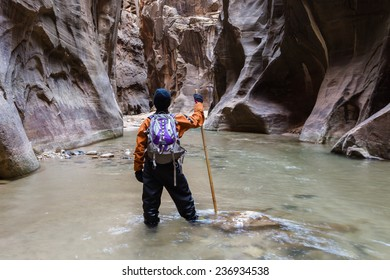 man hiking the Narrows in Zion National park with the virgin river flowing through the slot canyon