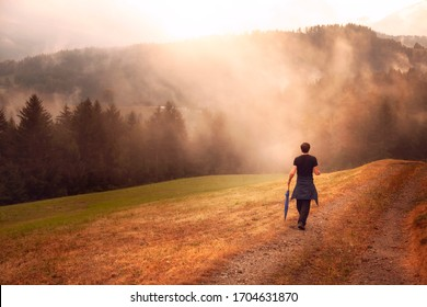 Man hiking on foggy morning countryside field.