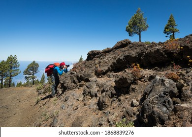 man hiking and photographing volcanic nature on canary islands