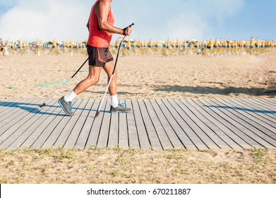 Man hiking with poles on wooden footpath of beach. Bibione Italy