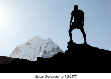 Man hiking silhouette in Himalaya mountains. Male hiker with backpack on top of mountain looking at beautiful morning at Mount Ama Dablam in Himalayas, Nepal