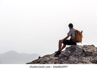 Man hiking silhouette in mountains, inspirational and motivation concept. Hiker with backpack on top of mountain looking at beautiful landscape.