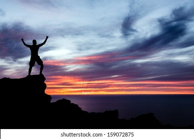 Man hiking silhouette in mountains, sunset and ocean. Male hiker with arms outstretched on top of mountain looking at beautiful night landscape.