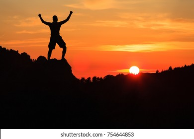 Man hiking silhouette in mountains, sunset and clouds. Male climber hiker arms outstretched on top of mountain after success climbing looking at beautiful sunset sky night landscape.
