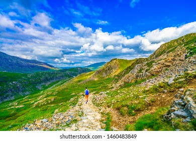 Man hiking in Snowdonia mountains with light backpack. Travel Lifestyle wanderlust adventure concept summer vacations outdoor alone into the wild