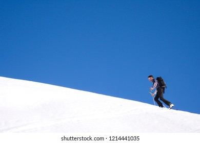 man hiking up a snowy mountain with skis underneath a blue sky in winter in the Swiss Alps