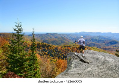Man hiking; standing on top of the mountain on edge of cliff, looking at beautiful autumn Blue Ridge Mountains landscape. North Carolina, USA