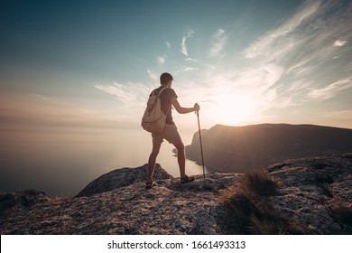 Man hiking at sunset mountains with heavy backpack. Travel Lifestyle wanderlust adventure concept summer vacations outdoor alone into the wild