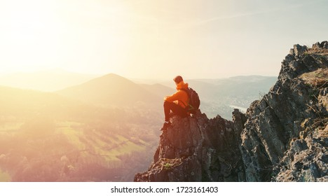 Man hiking at sunset mountains with heavy backpack. Golden hour time for photo