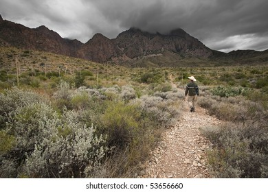 Man hiking through desert towards mountains near storm clouds