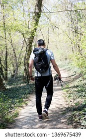 Man hiking through a forest wearing a backpack.