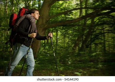 Man hiking through  forested area alone with backpack. Dark edges with motion blur to focus attention on hiker
