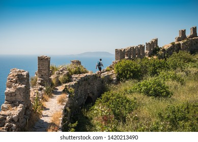 Man hiking through the historical wall of Navarino Castle, Pylos, Greece. A unique place explore an ancient fortress along the Aegean sea, with overgrown green vegetation, rock and blue skie