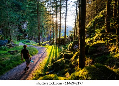 Man hiking with a waterbottle in hand, near kossvalsdalen in Norway. Sun going down in the forest, walking on a path.