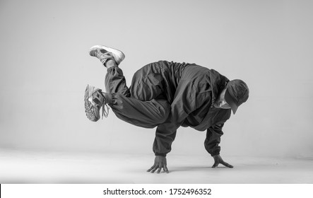 A man hip hop dancer or bboy freezes in one pose on a white background. Bboy doing stylish stunts.