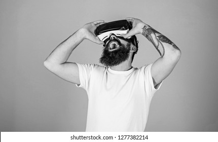 Man with hipster beard enjoying digital tech novelty. Excited bearded man watching movie in VR glasses, 3D experience concept. Artist with trendy beard and tattoo checking visualization of his work.