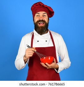 Man or hipster with beard holds kitchenware on blue background. Cook with excited face in burgundy uniform holds bowl and whisk. Bakery and cooking concept. Chef with red plate and whipping utensil