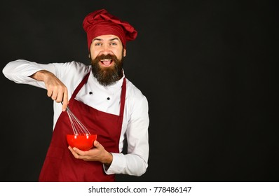 Man or hipster with beard holds kitchenware on black background. Chef with red plate and whipping utensil. Cooking process concept. Cook with happy face in burgundy hat and apron uses bowl and whisk