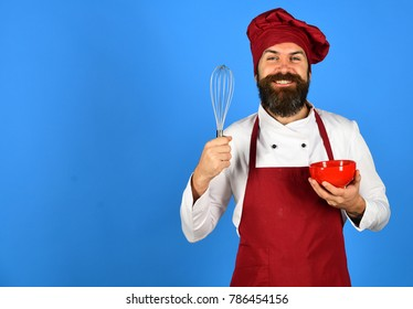 Man or hipster with beard holds kitchenware on blue background. Cook with happy face in burgundy uniform uses bowl and whisk. Chef with red plate and whipping utensil. Bakery and cooking concept