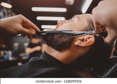 Man hipster having barber shave the barbershop.