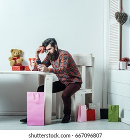 man or hipster, with long beard with smartphone sitting at table with cup, teddy bear, hearts, colorful bags, gift boxes in room on white wall. Valentines day, holiday. Technology