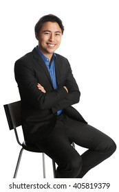 Man in his 20s sitting down on a chair against a white background, wearing a black suit with a dark blue shirt. Looking at camera with a big toothy smile.