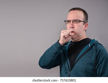A man in his 30's coughing into his has with space for your text in the background.