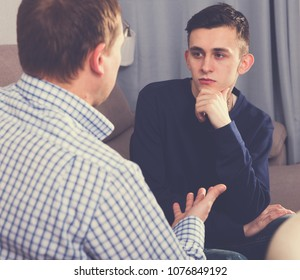 Man with his adult son are serious talking about life together at the home.