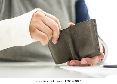 Man with his arm in a plaster cast holding a wallet removing money conceptual of the cost and expense of emergency medical treatment at a hospital or doctor