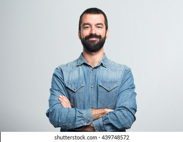 Man with his arms crossed over grey background