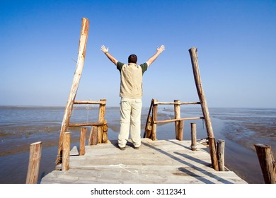 Man with his arms wide open on a dock