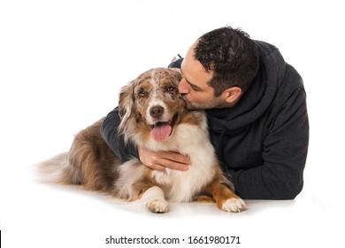 白い背景にオーストラリアの羊飼い犬を持つ男性